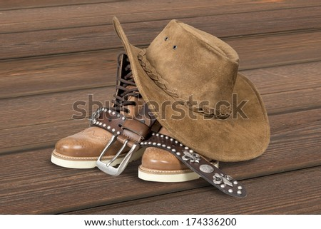 Cowboy hat and accessories over  wood plank background with clipping path.