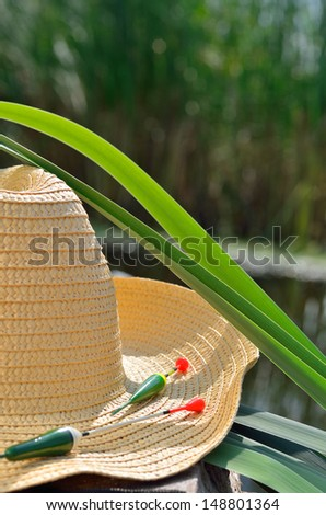 Cowboy hat, fishing floats and  reeds in the nature - stock photo