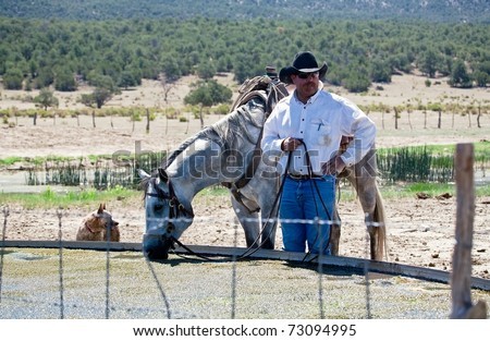 Cowboy holding reins while horse getting drink at water tank.  Remote Cibolla Canyon, Cibola County, New Mexico, USA. - stock photo