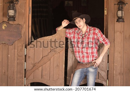 Cowboy in hat standing near saloon entrance, outdoors - stock photo