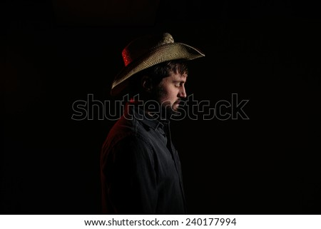 Cowboy in Studio Lighting body turned towards light looking down eyes closed - stock photo