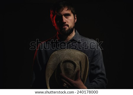 Cowboy in Studio Lighting holding hat on chest - stock photo