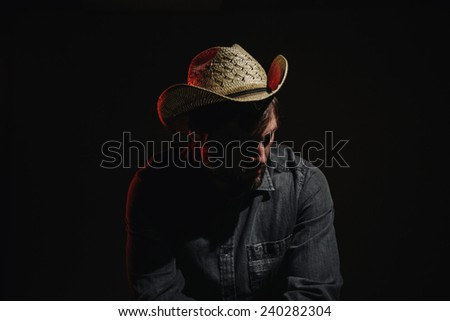 Cowboy in Studio Lighting leaning over chair looking down serious - stock photo