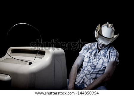 cowboy is sleeping while watching tv all alone - stock photo