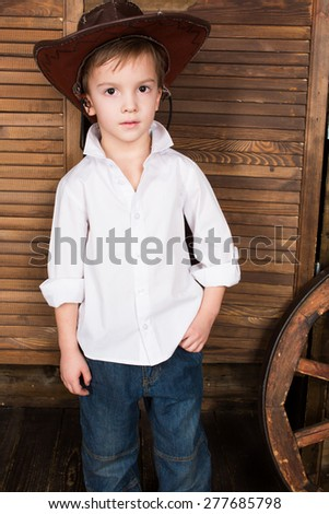 Cowboy kid white t-shirt jeans wooden background - stock photo
