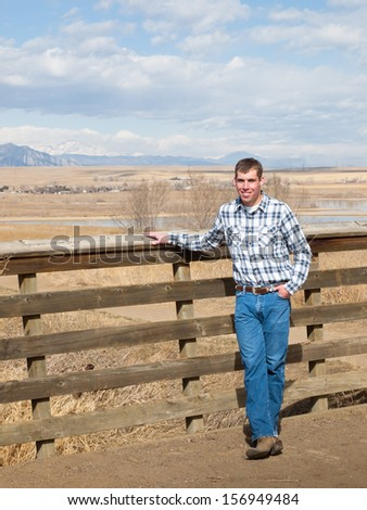 Cowboy next to the wooden fence in country side. - stock photo