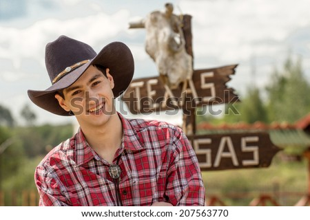 Cowboy on sign background. He is wearing a black cowboy hat. - stock photo