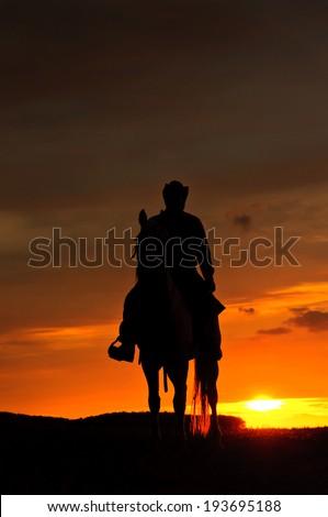 Cowboy riding his horse towards the sun - stock photo