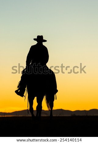 Cowboy silhouette on horse after sunset - stock photo