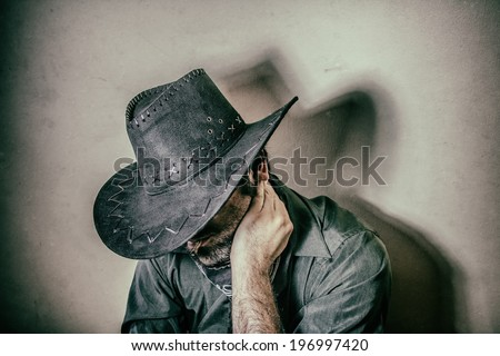 Cowboy Sits Alone. Cowboy with his head down and hand on neck, edited in vintage film style. - stock photo
