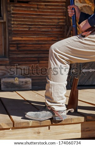 Cowboy steps up onto the wooden deck, showing off his dusty boots, spur and rifle - stock photo