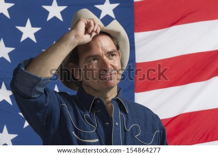 Cowboy tipping his hat in front of American flag, horizontal