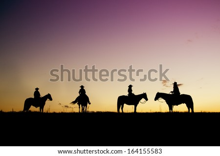Cowboys and cowgirl silhouettes at sunset