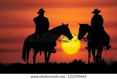 Cowboys, on horseback, silhouetted by the setting sun - stock photo
