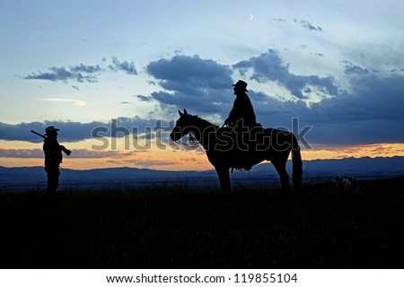 Cowboys silhouetted against a dawn Montana sky - stock photo