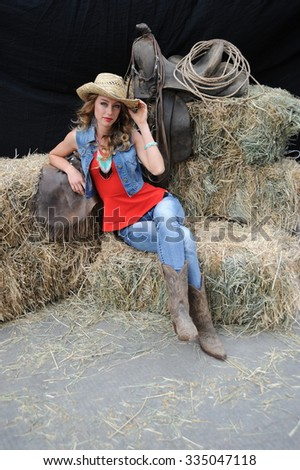Cowgirl beauty expressions on a haystack outdoors.