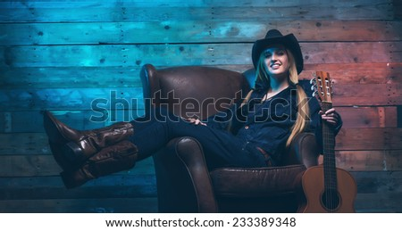 Cowgirl country singer with acoustic guitar. Sitting on leather chair. Wearing blue jeans and brown hat. In front of wooden wall. - stock photo