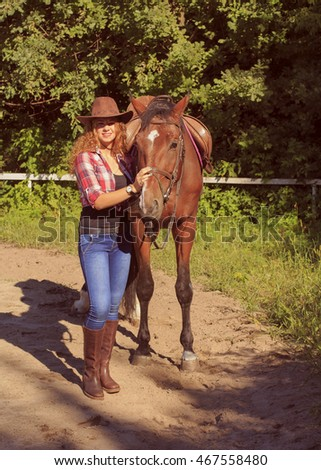 Cowgirl girl posing with horse outdoors portrait