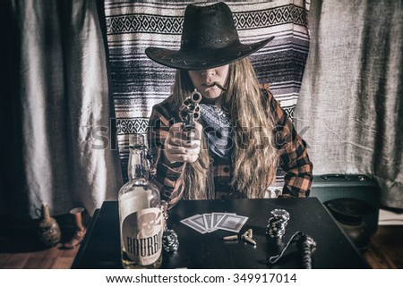 Cowgirl Gunslinger Sitting and Aiming. Old west cowgirl gunslinger sitting at table player poker with peacemaker gun pointed at camera, edited in vintage film style. - stock photo