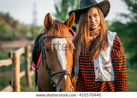 cowgirl in a hat standing near a horse in a field - stock photo