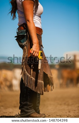 Cowgirl in branding yard holding syringe for calf - stock photo