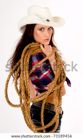 Cowgirl in Vertical Comp Wearing White Hat Carrying Rope and Gear - stock photo