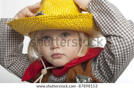 cowgirl is holding her yellow hat on her head with both hands, she is looking directly at the camera.