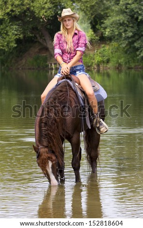 Cowgirl on a horse in the river, drinking the water. - stock photo