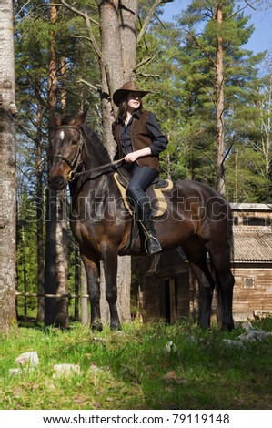 cowgirl on brown horse - stock photo
