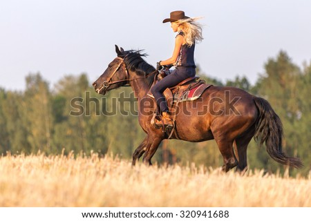 Cowgirl riding horse. - stock photo