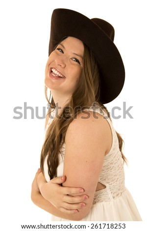 Cowgirl wearing a cowboy hat and a white sleeveless dress with her arms folded laughing