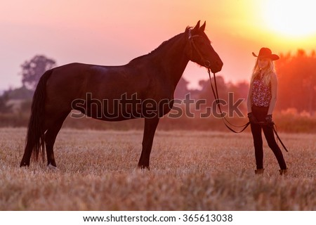 Cowgirl with a horse at sunset. - stock photo