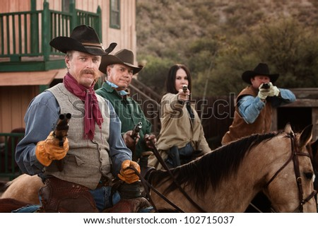 Cowgirl with three male companions in old American west scene