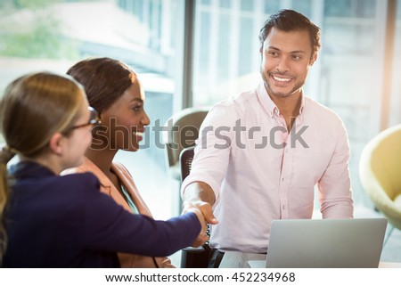 Coworker shaking hands with a colleague during meeting in the office - stock photo