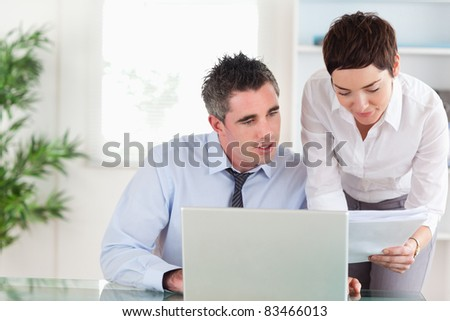 Coworkers comparing a blueprint document to an electronic one in an office