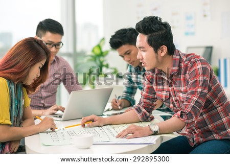 Coworkers discussing business project in the office