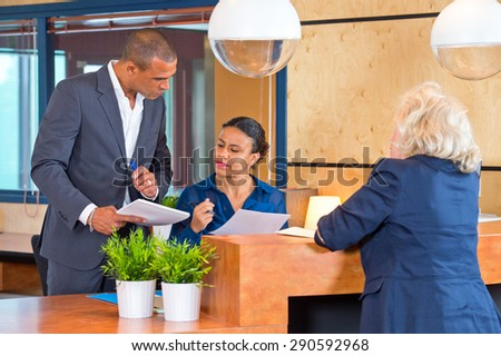 Coworkers discussing small matters with a secretary at a reception desk of a large corporate company - stock photo