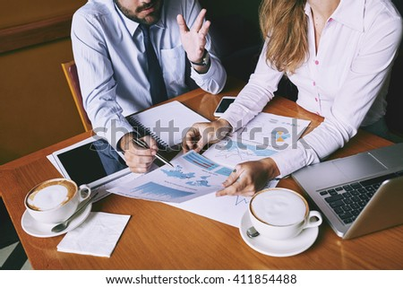 Coworkers examining business reports at meeting