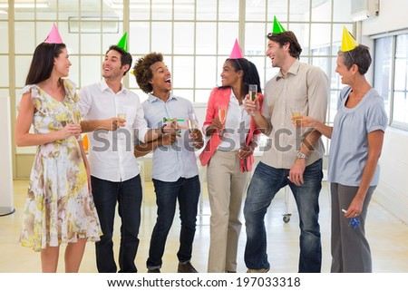 Coworkers laugh and celebrate accomplishment and enjoy party in the office - stock photo