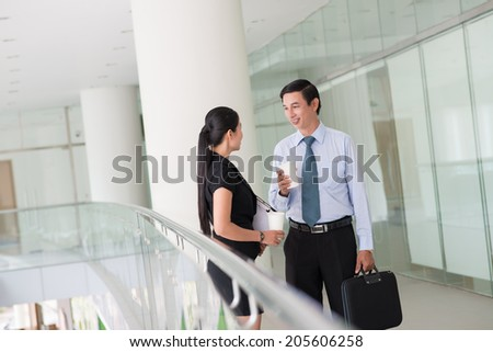 Coworkers talking in the office building - stock photo
