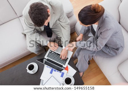 Coworkers using laptop together sitting on sofa at office - stock photo