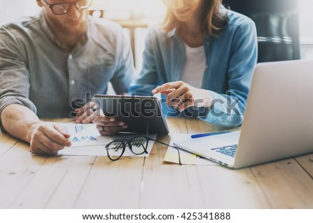 Coworkers work creative studio.Producers meeting,working new project.Young business crew with startup.Laptop computer on wood table,creative idea presentation.Blurred,film effect.Horizontal - stock photo