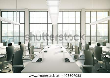 Coworking area in office interior with notebooks on tables, ceiling lamps and city view. 3D Rendering