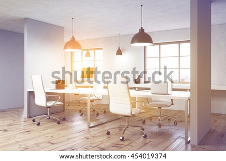 Coworking office interior with wooden floor, concrete walls, ceiling lamps, computer monitors on desks, windows with city view and sunlight. Toned image, 3D Rendering