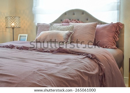 Cozy  and classic  bedroom interior with pillows and reading lamp on bedside table - stock photo