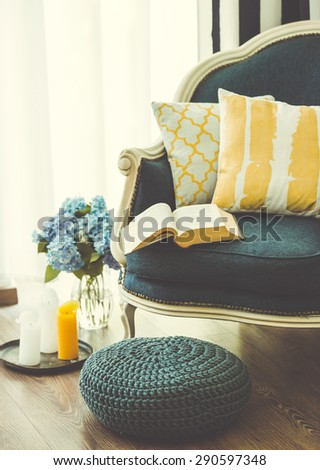 Cozy armchair with open book and decorative pillows. Interior and home decor concept. Toned image - stock photo