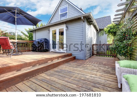 Cozy backyard deck with table set under umbrella and wicker ottomans with green pillows - stock photo
