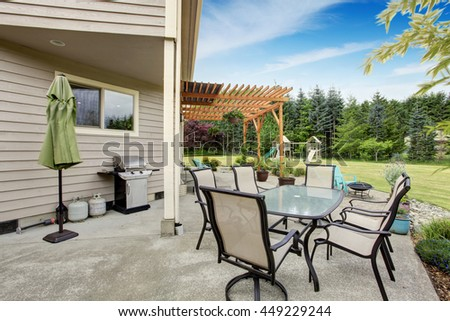 Cozy backyard patio area with table set and nice landscaping desing. Also playground at the background - stock photo