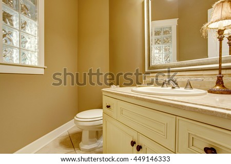 Cozy bathroom interior with decorative lamp on old white cabinets,  yellow walls and toilet.