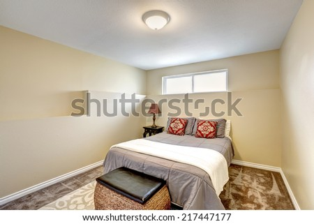 Cozy bedroom in soft ivory tones with brown carpet floor.Grey bedding with red pillows and white blanket
